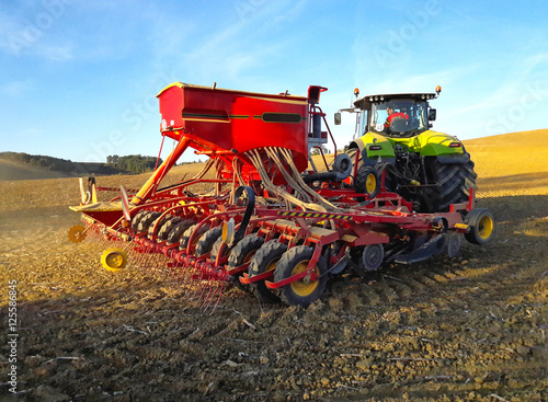 Poster Tracteur de labour sur un champ de terre