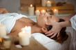 Leinwanddruck Bild - Young beautiful girl having face massage relaxing in spa salon.