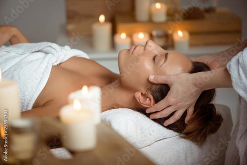 Leinwanddruck Bild Young beautiful girl having face massage relaxing in spa salon.