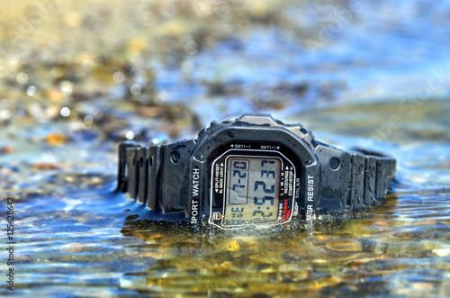 Electronic waterproof watch, immersed in the water stream. Poster
