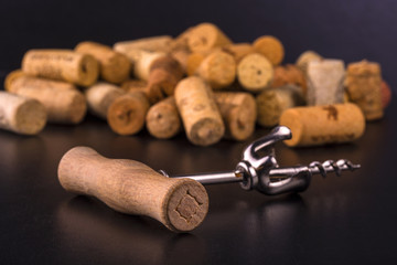 Wine corks and corkscrew on black  table