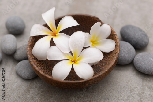 Plexiglas Spa Beautiful Composition of frangipani in wooden bowl with spa stones