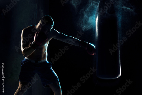 Poster Male boxer boxing in punching bag