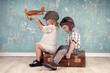 Urlaubskonzept, zwei kleine Kinder mit Koffer und Flieger