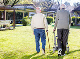 Pensioner friends with handicap walking outdoor in garden, back - 125717014