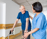 Happy elder man with walker talking to nurse in hospital corrido