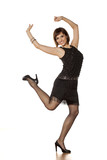 happy middle-aged woman with short black dress dancing on a white background