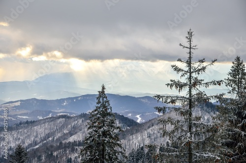 Obraz Winter mountain landscape. High mountain peaks through the clouds.
