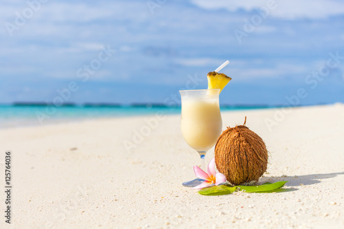 Fotobehang Plumeria Pina Colada cocktail on the beach with coconut and exotic flower