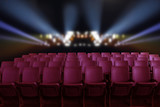 Empty theater auditorium or cinema with red seats and lighting  - 125779281
