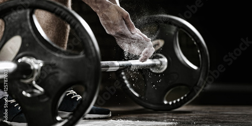 Poster Sports background. Young athlete getting ready for weight lifting training. Powerlifter hand in talc preparing to bench press
