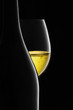 Bottle and glass of white wine on a black