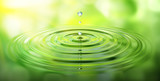 Wassertropfen und Wellen mit grüner Spiegelung