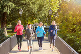Four young women jogging over bridge