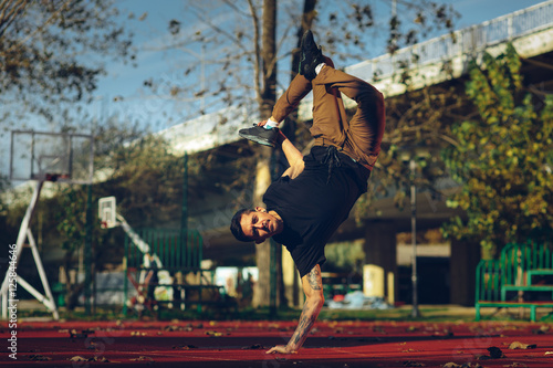 BBoy doing handstand on basketball court Poster