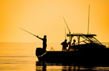 silhouette of sport fishing boat reflecting on calm water - 125861407