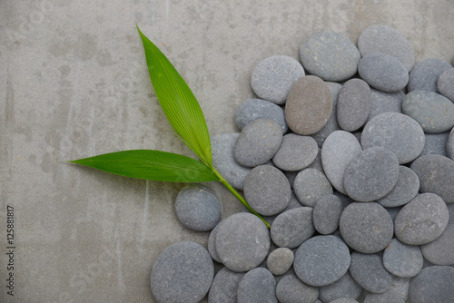 Poster Spa pile of stones with bamboo leaf-gray background