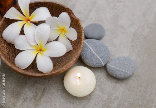 Poster Spa frangipani in wooden bowl with spa stones ,candle on grey background.