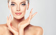 Постер, плакат: Beautiful Young Woman with Clean Fresh Skin touch own face Facial treatment  Cosmetology beauty and spa