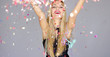 Sexy, blond girl blowing confetti from her hands to camera direction. She dancing and having fun on a new year party. Smiling to the camera.