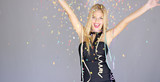 Happy and sexy young woman in evening dress, wrapped in new year party serpentines and floating confetti, dancing while isolated on gray background. She looking at camera and smiling.