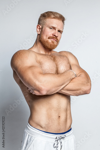 young caucasian muscular bearded man isolated on studio background Poster