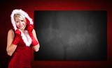 attraktive Weihnachtsfrau vor leerer Kreidetafel