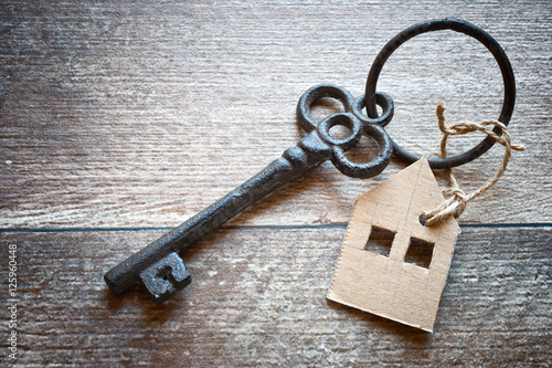 Poster old metal key with symbol of a family house on the wooden background
