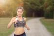 Junge Frau hört Musik mit dem Smartphone beim Jogging