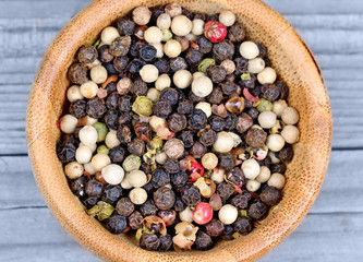 Colorful peppercorns in a bamboo bowl on wooden table