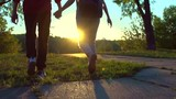 Happy joyful young couple walking in a park together, holding hands. Slow motion 240 fps. Full HD 1080p