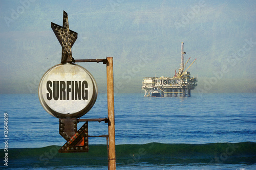 Poster surfing sign with oil platform in background
