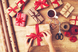 hand of woman  packs boxes with Christmas gifts
