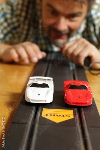 Fotobehang F1 Spielzeugautorennbahn, Mann mit Drücker