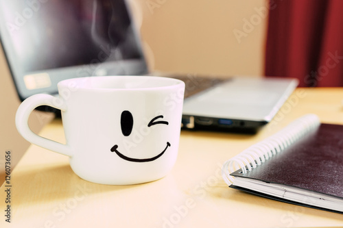 Smiling cup, notepad and laptop on the desk Poster