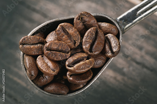Poster group of coffee beans on a spoon