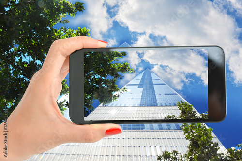 Woman hand with smartphone tacking a picture at One World Trade Center, Manhatta Poster