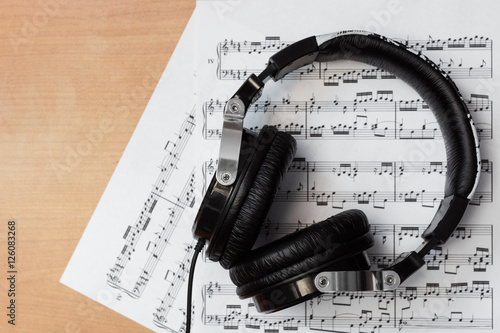 Audífonos y partituras en escritorio de madera Плакат