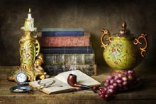 Classique encore la vie avec des antiquités, livres anciens, vieux tuyaux, verres, montre de poche et les raisins sur la table en bois rustique.