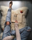 woman on the fur carpet with old book, top view - 126100838