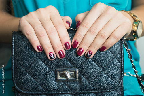 Aluminium Manicure Female nails with red nail polish and a beautiful black handbag