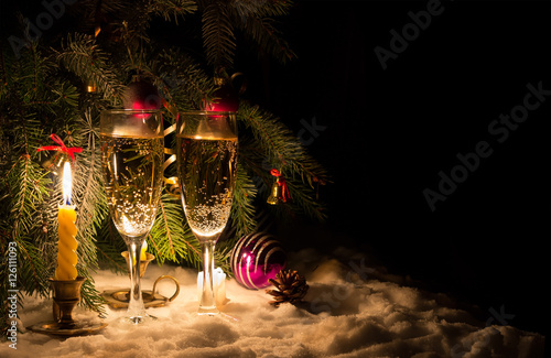 Champagne glasses and glowing candles on snow