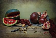 Classique toujours la vie avec la pastèque et la grenade placée dans la plaque d'argent vintage avec un foulard soyeux rouge, un peu de noix et l'écrou concasseur sur la table en bois rustique.