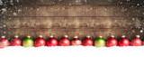 Weihnachtskugeln im Schnee vor einer Holzwand