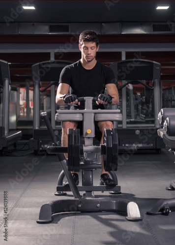 man seated calf raise machine, gym. Poster