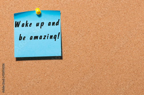 Poster Wake Up and Be Amazing message text written on blue sticker pinned at cork notic
