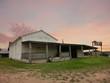 Texas rural farmhouse at dusk with pastel sky