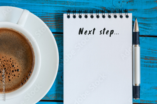 Next Steps inscription written in notepad near morning coffee cup. Business, technology, internet concept. Stock Image