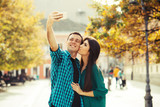 Young couple taking selfie in the main street at sunny day