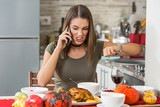 Angry young woman is sitting at dining table and yelling on her boyfriend on the phone for being late for dinner again.